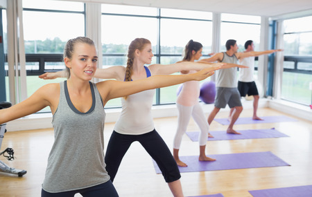 Sporty people stretching hands at yoga class in fitness studio photo