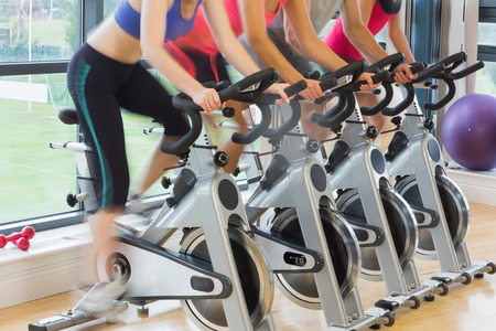 Mid section of four people working out at spinning class in gym