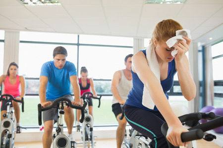 Determined and tired people working out at spinning class in gym photo