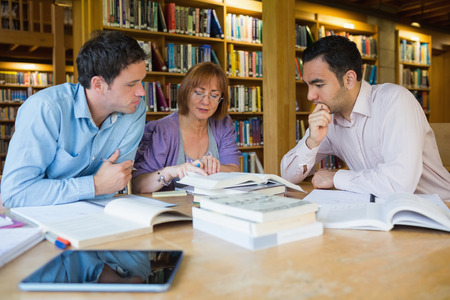 Three mature students studying together in the library photo