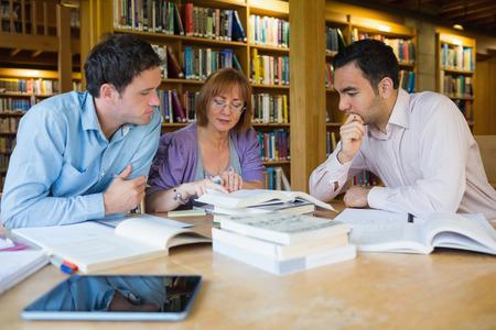 alumnos estudiando: Tres estudiantes adultos que estudian juntos en la biblioteca