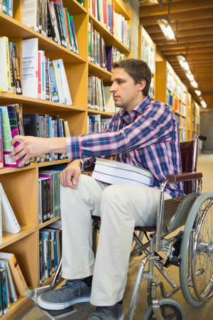 Full length of a man in wheelchair selecting book from bookshelf in the library photo