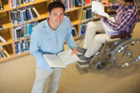 High angle view of a man by disabled student in wheelchair against bookshelf in the library photo