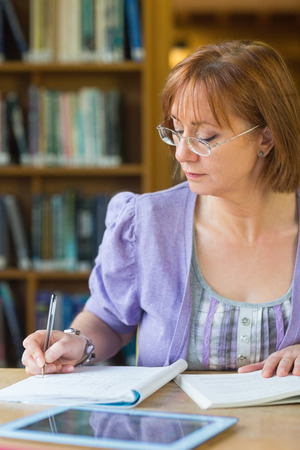 Close-up of a mature female student writing notes at desk in the library photo