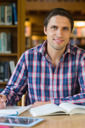 Portrait of a smiling mature male student sitting at desk in the library photo