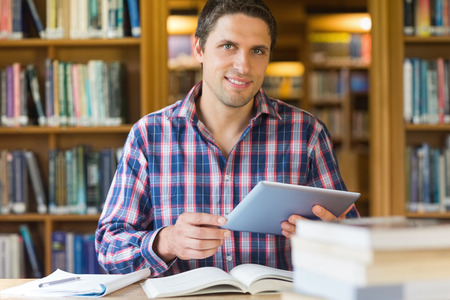 Portrait of a happy mature male student holding tablet PC in the library photo