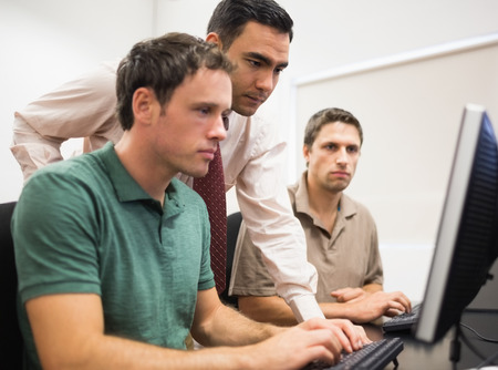 30s adult: Concentrated teacher with mature students using computer in the computer room Stock Photo