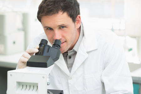Close-up portrait of a male scientific researcher using microscope in the laboratory photo
