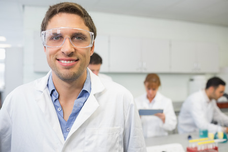 Portrait of a smiling scientist with colleagues at work in the laboratory photo