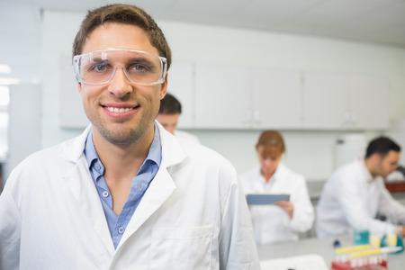 examenes de laboratorio: Retrato de un cient�fico sonriendo con sus colegas en el trabajo en el laboratorio