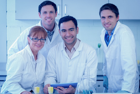 Group portrait of smiling scientists with tablet PC in the laboratory photo