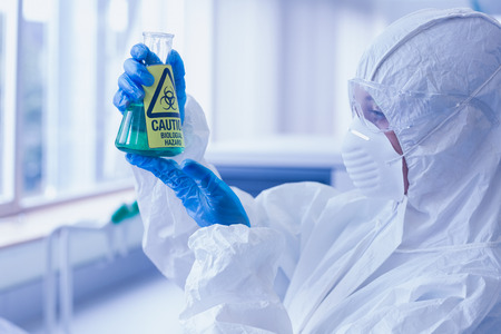 Close-up side view of a scientist in protective suit looking at hazardous blue chemical in flask at the laboratory Stock Photo