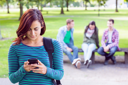 Portrait of college girl text messaging with blurred students sitting in the park photo