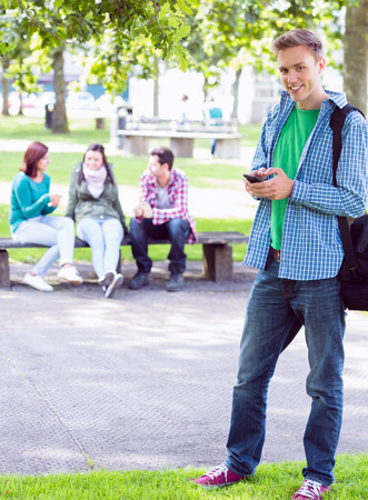 Portrait of a smiling college boy text messaging with blurred students sitting in the park photo