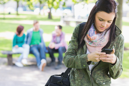 College girl text messaging with blurred students sitting in the park photo