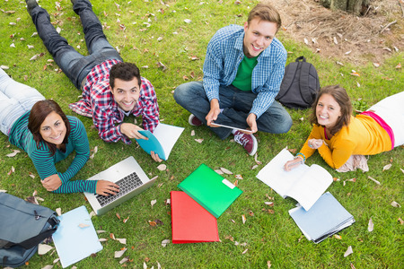 High angle portrait of young college students using laptop while doing homework in the park photo