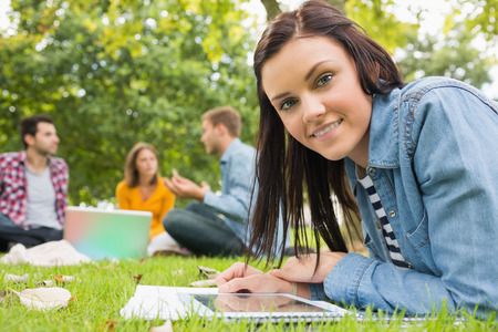 Portrait of a smiling female with tablet PC while other students using laptop in background at the park photo