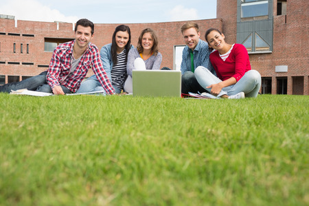 Group portrait of young students with laptop in the lawn against college building photo