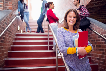 Portrait of a smiling female holding books with students behind on stairs in the college photo