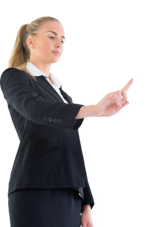 Low angle view of young businesswoman pointing upwards on white screen photo