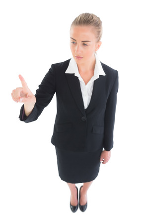 High angle view of young ponytailed businesswoman pointing upwards on white screen photo