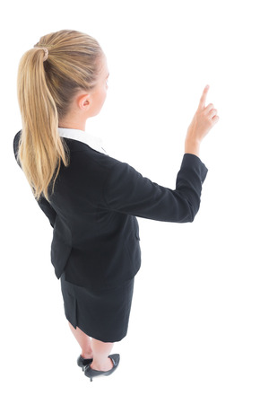 High angle view of young business woman pointing on white background photo