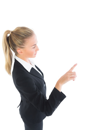 Blonde ponytailed business woman pointing on white background photo
