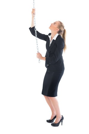 Chic businesswoman pulling a chain on white background photo