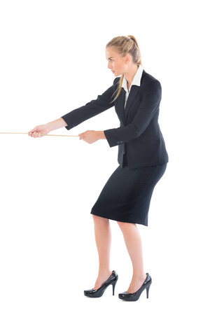 Focused blonde businesswoman pulling a rope on white background photo