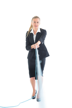 Focused blonde businesswoman using a hose looking at camera photo