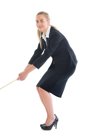 Smiling ponytailed business woman pulling a rope on white background photo