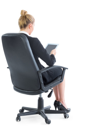 Well dressed young businesswoman sitting on an office chair using her tablet photo