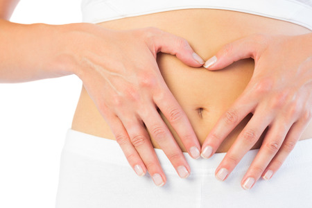 Close up picture of fit woman holding her belly on white background