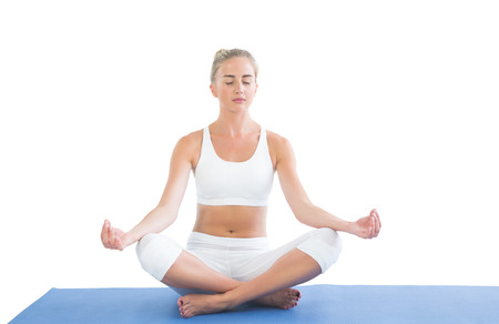 Toned relaxed blonde sitting in lotus pose on white background photo