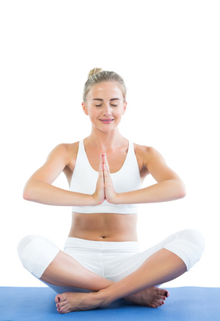 Toned smiling blonde sitting in lotus pose meditating on white background photo