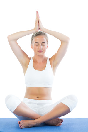Toned calm blonde sitting in lotus pose meditating on white background photo