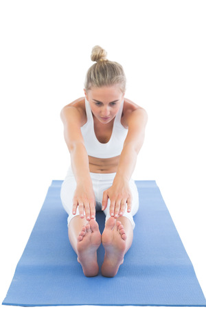 touching toes: Toned focused blonde sitting on exercise mat stretching legs on white background Stock Photo