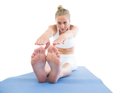 touching toes: Toned calm blonde sitting on exercise mat stretching legs on white background Stock Photo
