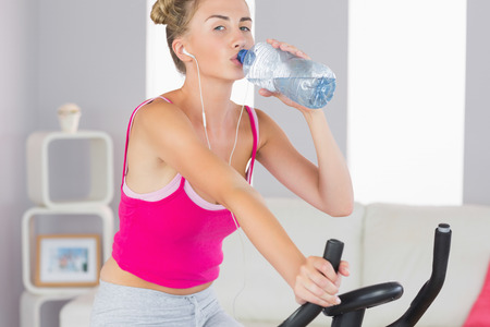 Sporty blonde training on exercise bike drinking water in bright living room photo