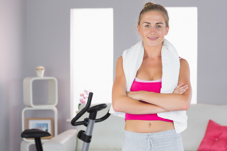 cross armed: Sporty smiling blonde standing cross armed in bright living room Stock Photo