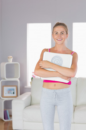 cross armed: Sporty cheerful blonde standing cross armed holding scales in bright living room