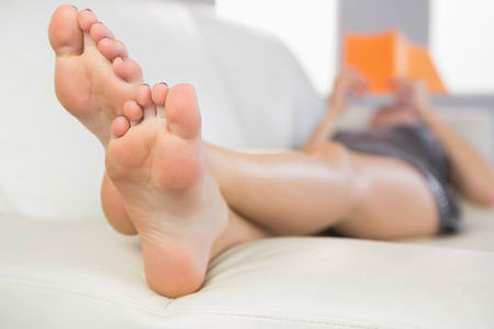 Close up picture of feet from woman lying on couch in bright living room photo