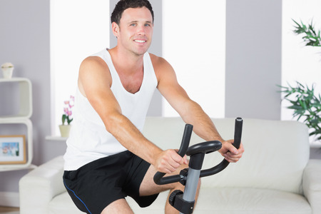 Cheerful sporty man exercising on bike in bright living room photo