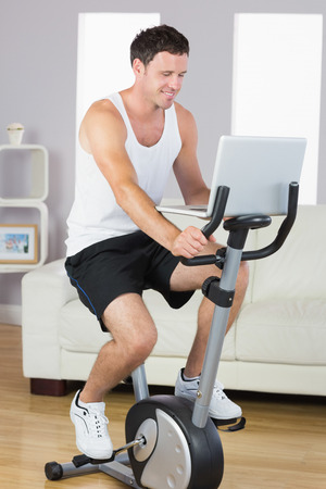 Happy sporty man exercising on bike and using laptop in bright living room photo