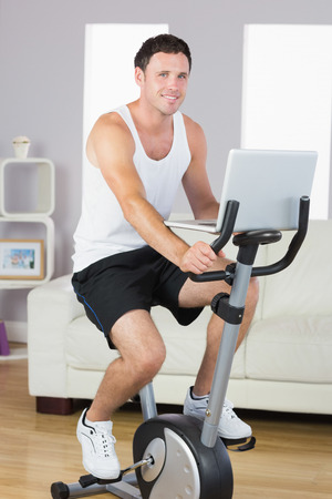 Smiling sporty man exercising on bike and holding laptop in bright living room photo