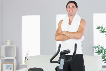 cross armed: Cheerful sporty man standing next to exercise bike cross armed in bright living room