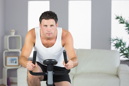 Handsome sporty man exercising on bike in bright living room photo