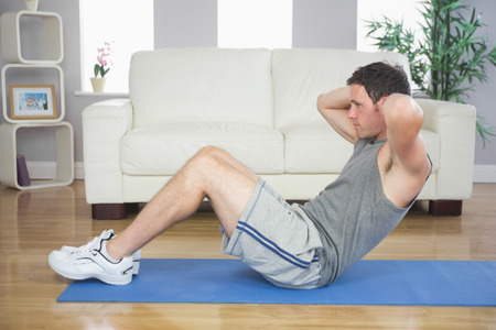 Fit handsome man doing sit ups in bright living room photo