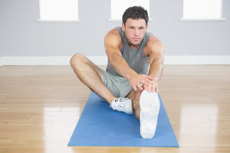 touching toes: Handsome sporty man stretching his right leg in bright room