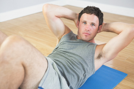 sit ups: Calm sporty man doing sit ups on blue mat in bright room